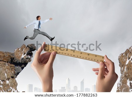 Young businessman in suit jumping over mountain gap - stock photo