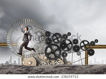 Young businessman in suit running in hamster wheel - stock photo