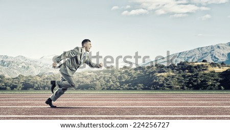 Young businessman in suit running on stadium track - stock photo