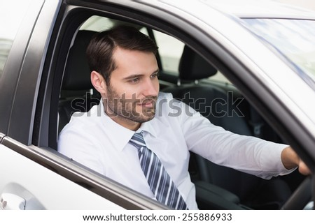 Young businessman in the drivers seat in his car - stock photo