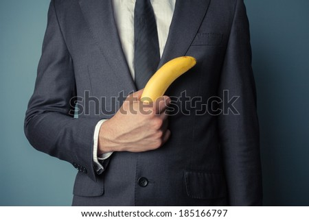Young businessman is holding a banana - stock photo