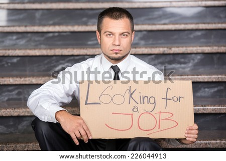 Young businessman is holding sign Looking for a job, sitting on the stairs. - stock photo