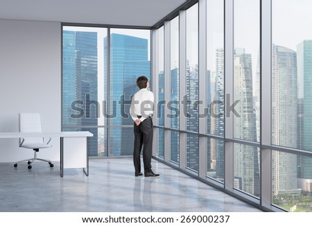 Young businessman is looking through the corner window. Singapore background. - stock photo