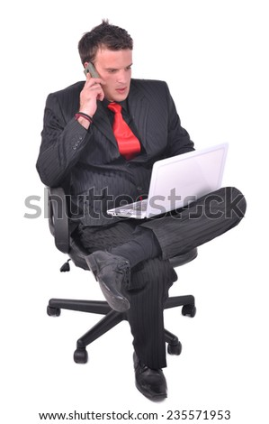 Young businessman is sitting on the chair and talking on his smartphone and checking email - stock photo