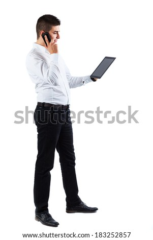 Young businessman is using his tablet while talking on the phone - isolated on white - stock photo