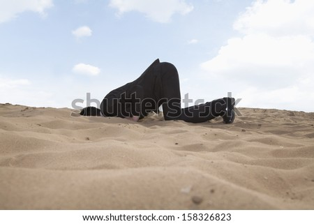 Young businessman kneeling with his head in hole in sand - stock photo