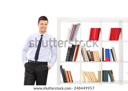 Young businessman leaning on a bookshelf isolated on white background - stock photo