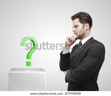 Young  businessman look at the green question mark on a white pedestal. On a gray background - stock photo