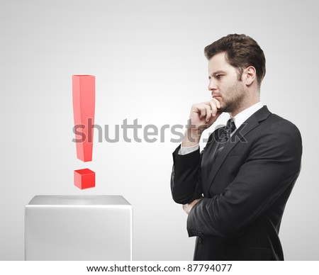 Young  businessman look at the red exclamation mark on a white pedestal. On a gray background - stock photo