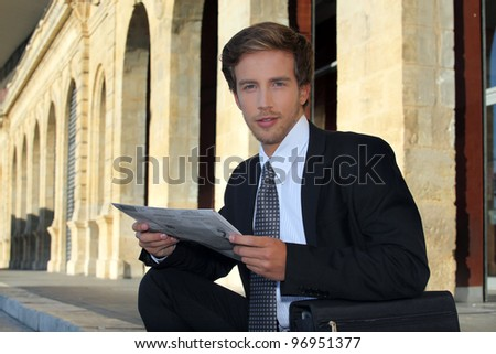 Young businessman looking at a paper - stock photo