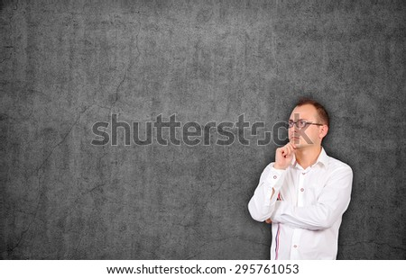 young businessman looking at blank concrete wall - stock photo