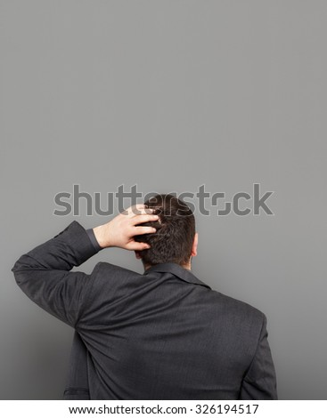 Young businessman looking at blank wall - stock photo