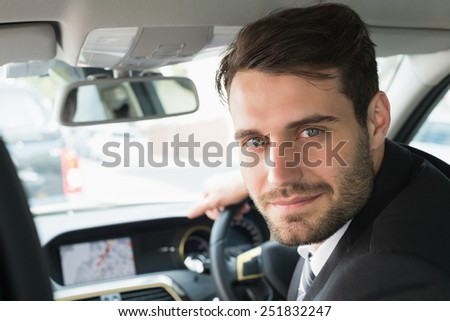 Young businessman looking at camera in his car - stock photo