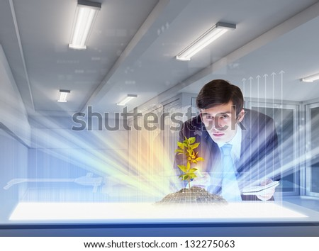 young businessman looking at high-tech image of sprig - stock photo