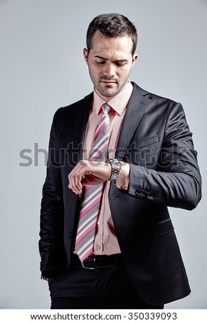 Young businessman looking at his wrist watch isolated over grey - stock photo