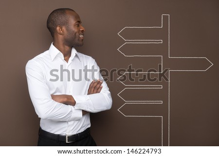 Young businessman looking at many arrows on the brown wall - stock photo