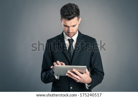 Young businessman looking at tablet against dark background.  - stock photo