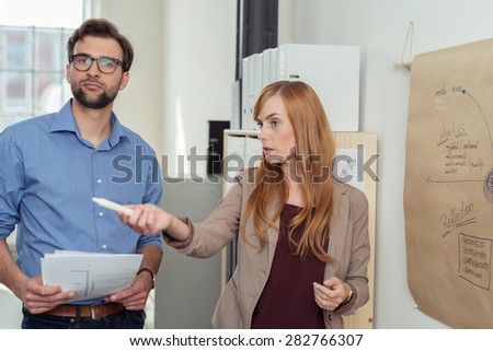 Young Businessman Looking at the Camera While his Partner is Discussing the Project Plans Seriously. - stock photo