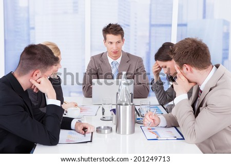 Young businessman looking at tired colleagues during conference meeting - stock photo