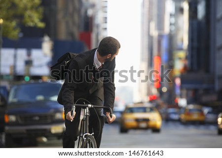 Young businessman looking over shoulder while riding bicycle on urban street - stock photo