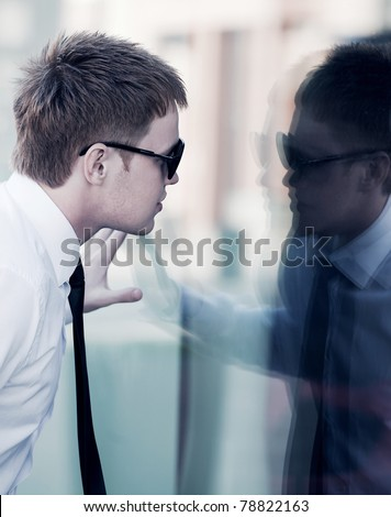 Young businessman looking through a window - stock photo