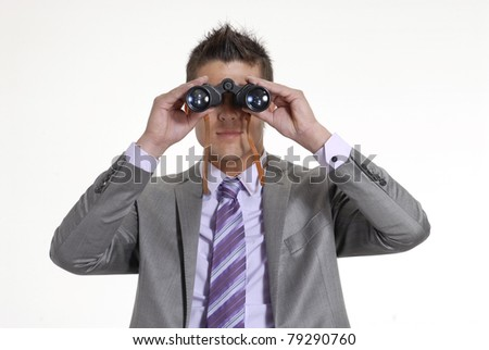Young businessman looking through binoculars on white background. - stock photo