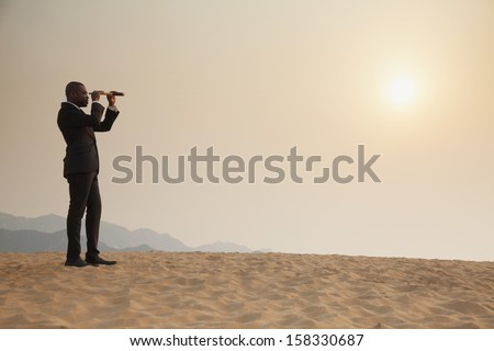 Young businessman looking through telescope in the middle of the desert - stock photo
