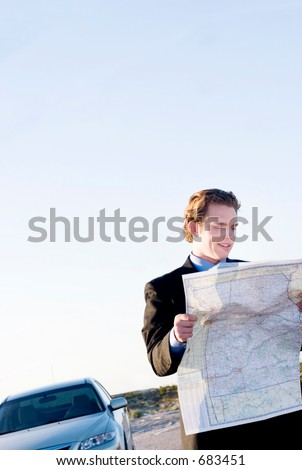 young businessman lost in the desert using a map - stock photo