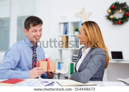 Young businessman making Christmas surprise to his colleague in office - stock photo
