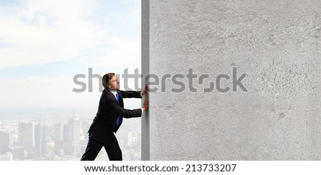 Young businessman making effort to move stone wall - stock photo
