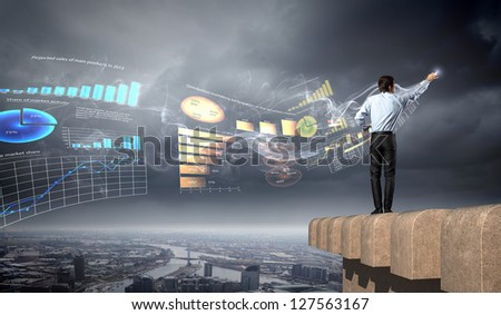 young businessman man standing with back drawing diagram against city background - stock photo