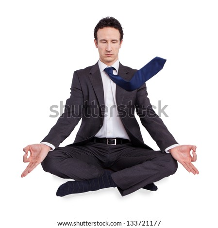 young businessman meditating in yoga lotus pose on white background - stock photo