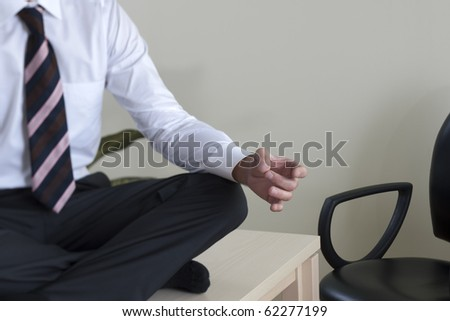 Young businessman meditating on his desk - stock photo