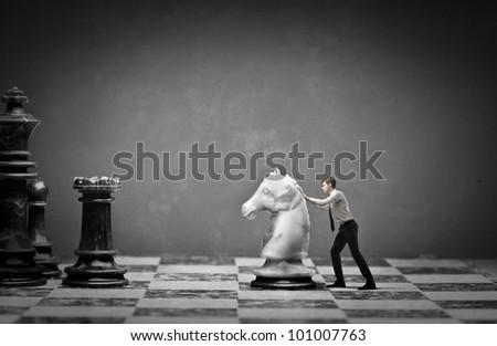 Young businessman moving a knight on a chessboard - stock photo