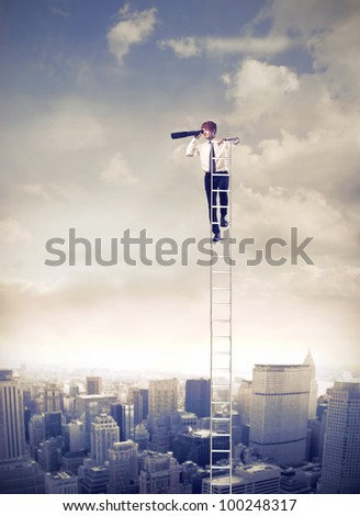 Young businessman on a ladder over a big city using binoculars - stock photo