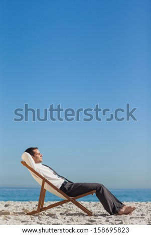 Young businessman  on the beach relaxing and tanning on his deck chair  - stock photo