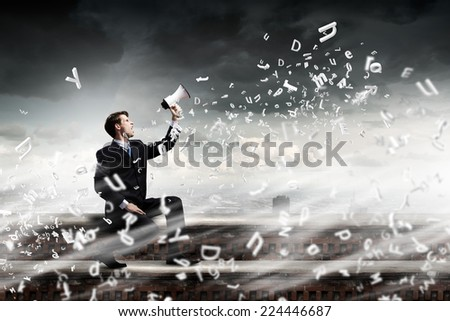 Young businessman on top of building screaming in megaphone - stock photo