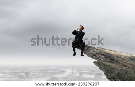Young businessman on top of rock screaming in megaphone - stock photo
