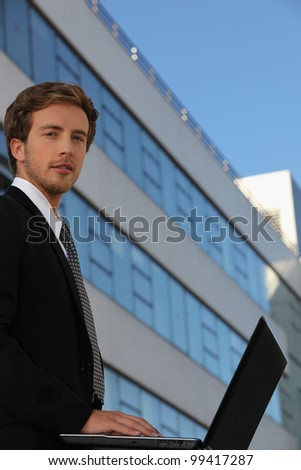 Young businessman outside a modern office building - stock photo