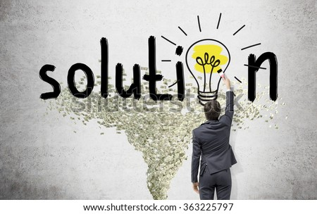 Young businessman painting a bright yellow bulb with a brush in the word 'solution' instead of the second 'o' on the white wall. Dollar tornado under it. Back view. Concept of finding a solution. - stock photo