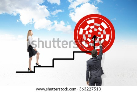 Young businessman painting a red target with a brush, a businesswoman ascending a black painted ladder leading to it, blue sky with clouds at the background. Back view. Concept of setting a goal. - stock photo