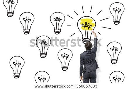 Young businessman painting black bulbs with a roller on the white wall, one of them is yellow. Back view. Concept of finding a suitable solution. - stock photo