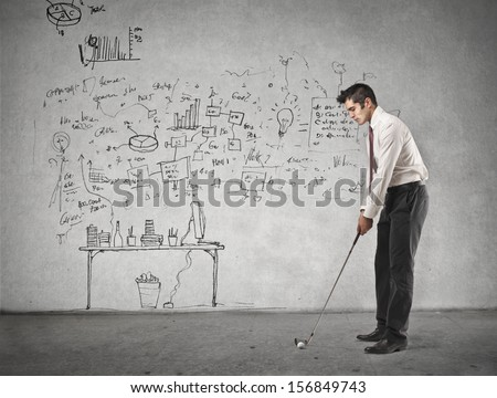 young businessman playing golf in the office - stock photo