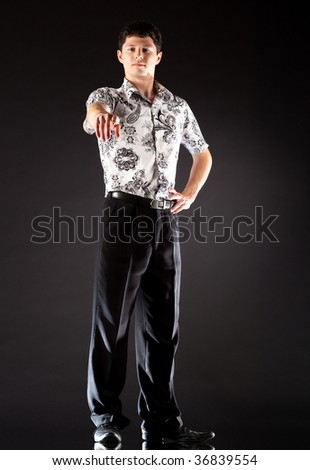 Young businessman pointing. On dark background. - stock photo