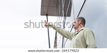 Young businessman pointing to sky at business center - stock photo