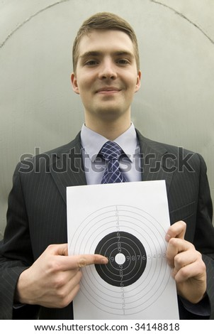 Young businessman points right at the bull's-eye - stock photo