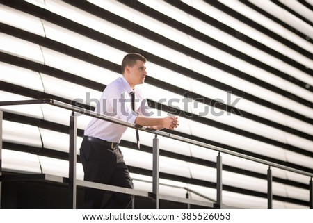 Young businessman portrayed in front of the modern office building. He is leaning on the railing of the balcony, looking into the distance. - stock photo