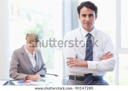 Young businessman posing while his colleague is working in a meeting room - stock photo
