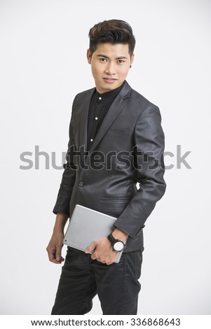 Young businessman posing with digital tablet on white. - stock photo