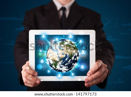 Young businessman presenting 3d earth globe in tablet - elements of this image furnished by NASA - stock photo